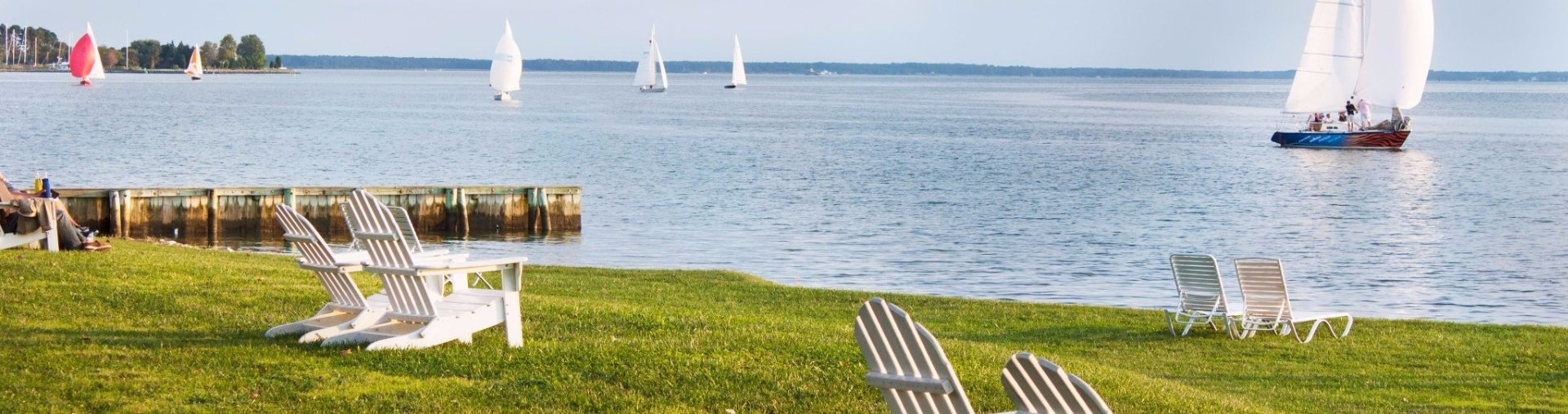 Chairs on a lawn facing sailboats in the water